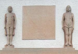 Unverdeckt sind das Mädchen un der Junge über dem links danebenliegenden Eingang zur Schulturnhalle.