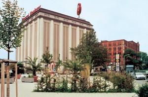Monumentale historische Gebäude erinnern heute noch an die Blütezeit der Sinner AG. Blick von der neuen Grünwinkler Mitte auf das Silogebäude und die (rote) Mühle im Hintergrund.